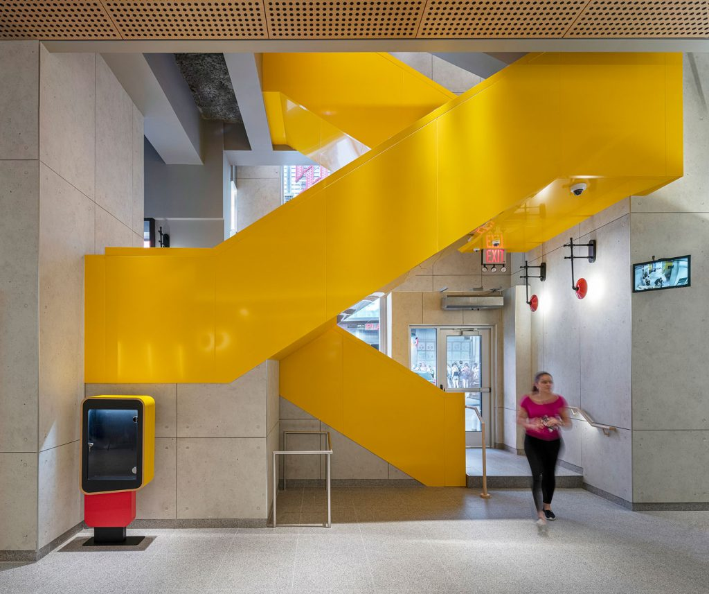 Interior of McDonalds featuring a bold yellow staircase.